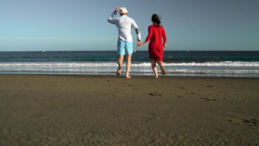 Couple in love carefree running to the water on the beach. Picturesque ocean coast of Tenerife, Canarian Islands, Spain