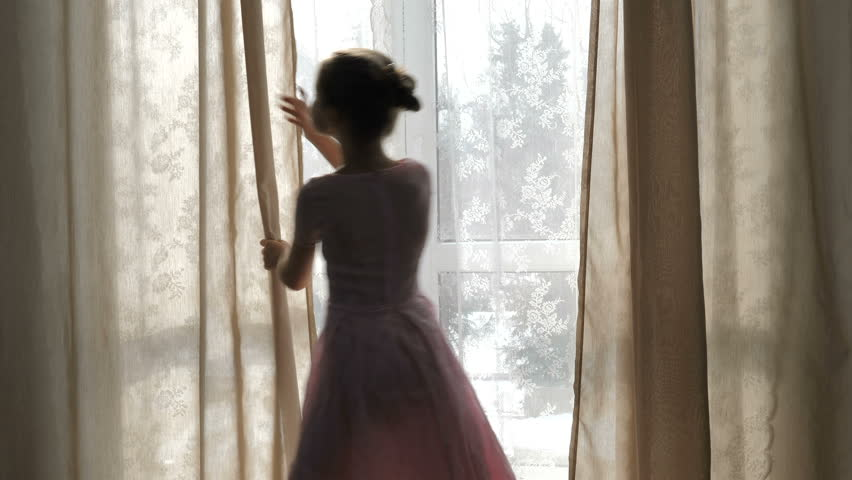 Girl in a pink dress opens curtains in the morning