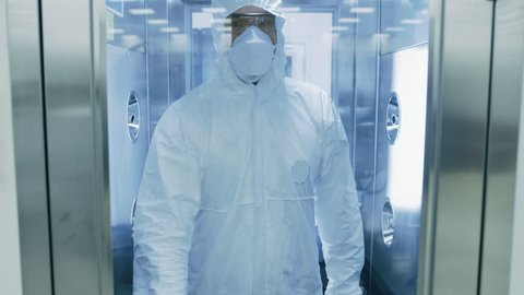 Scientist / Virologist / Factory Worker in Coverall Suit Disinfects Himself in Decontamination Shower Chamber. Biohazard Emergency Response.