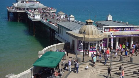 NORFOLK, ENGLAND, JULY 22ND, 2018: During a long UK heatwave, people enjoying the sunshine at historic Cromer pier, on the north Norfolk coast in England, UK. Slow motion.