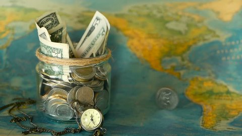 Travel budget concept. Money saved for vacation in glass jar on world map background, copy space. Banknotes and coins for adventure. Savings for journey. Collecting money for trip. Moneybox with cash.