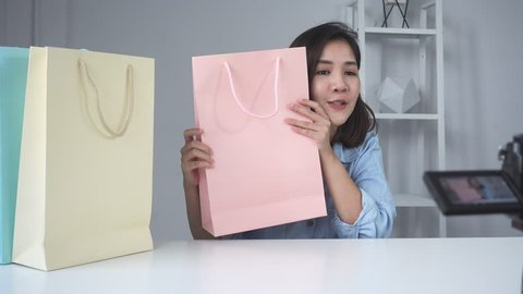 b90a1eedd9 Happy beautiful Asian woman unboxing gifts from brand or her subscribers.  Female blogger recording video