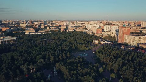 Aerial drone flight over the huge park with mixed forest in the center of Chelyabinsk city, sunny evening in the capital of South Ural, Russia