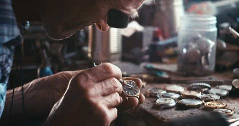 The old watchmaker is repairing the vintage hand watch in his workshop. RED camera shot. 4k footage.