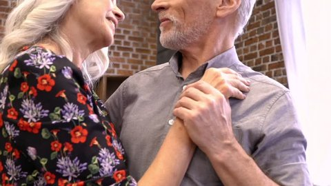 Cropped view of lovely elderly couple dancing together at home