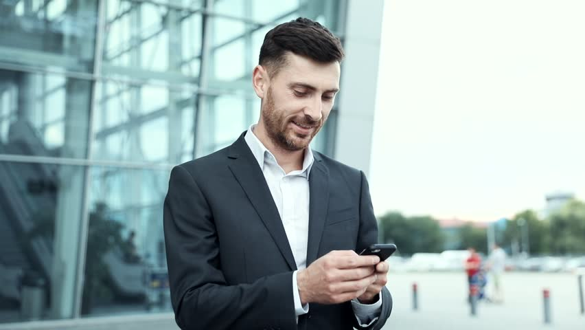 Young Handsome Man Wearing Elegant Suit. Checking Mails on his Smartphone. Working on it while Standing near Office. Attractive Bearded Businessman. Business Lifestyle. | Shutterstock HD Video #1014544436