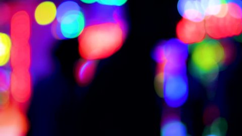 Defocused funny atmosphere at the amusement park in megapolis with multiple colorful lights