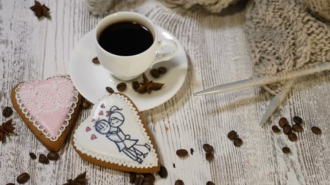 Love concept. Saint Valentine Day. a cup of fresh brewed coffee and a heart shaped ginger cookie on wooden background. Female hand places a forgive me note near