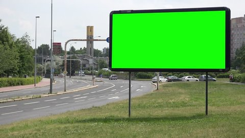 A billboard with a green screen by a road in an urban area