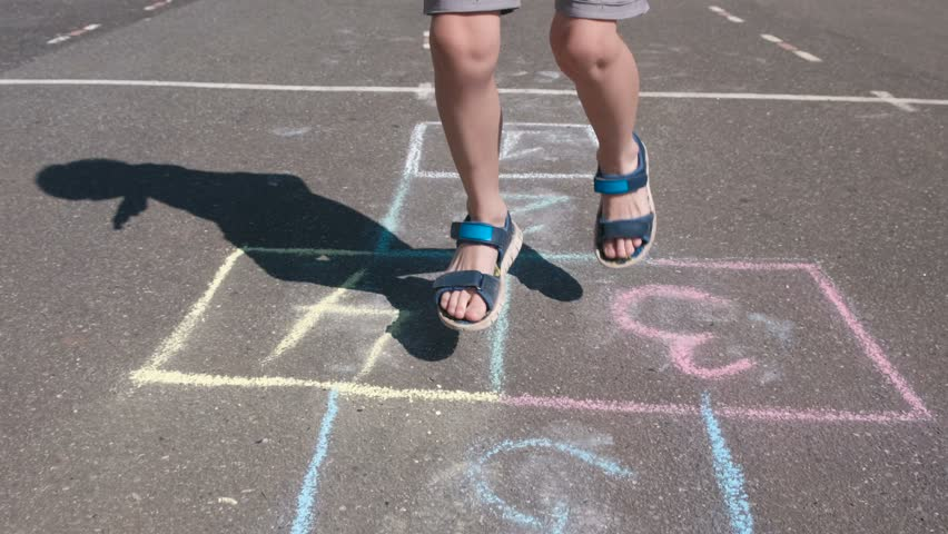 Boy jumps playing hopscotch in the street. Close-up legs. #1014590516
