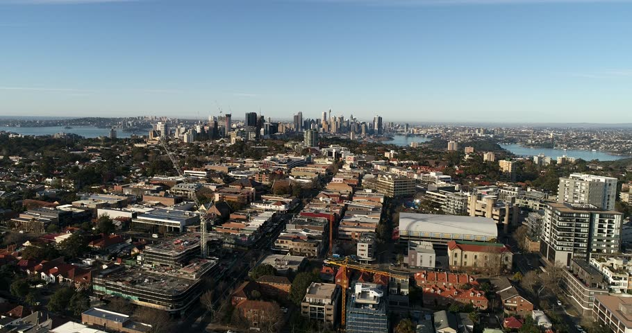 Flying away from North Sydney CBD towers and distant city landmarks over local residential suburb of St Leonards with quiet streets and town houses.
