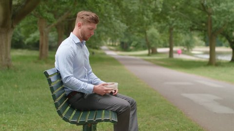 Man Sitting On Bench Eatc Lunch and Experiences Heartburn Pain