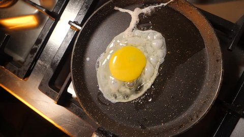 Fried egg in a pan. Fried egg preparation on a frying pan.