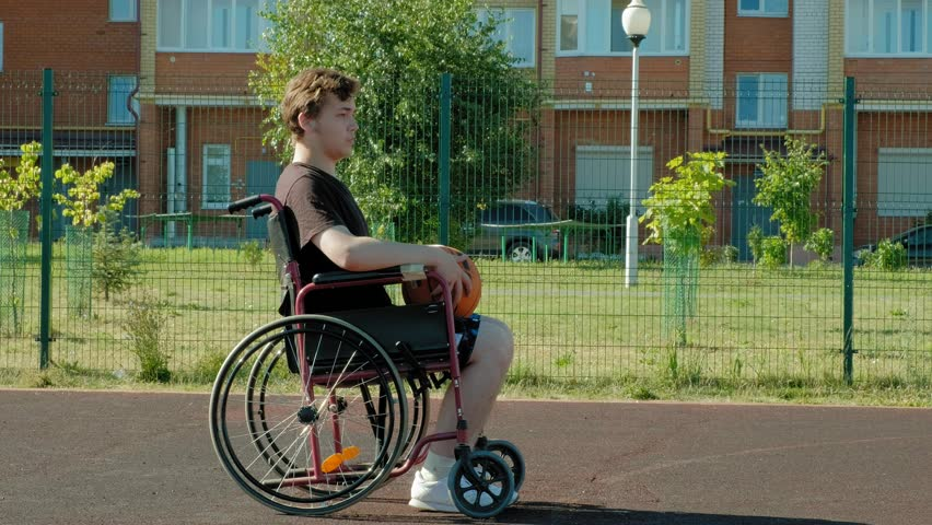 Disabled man plays basketball from his wheelchair, On open air 4k | Shutterstock HD Video #1014696386