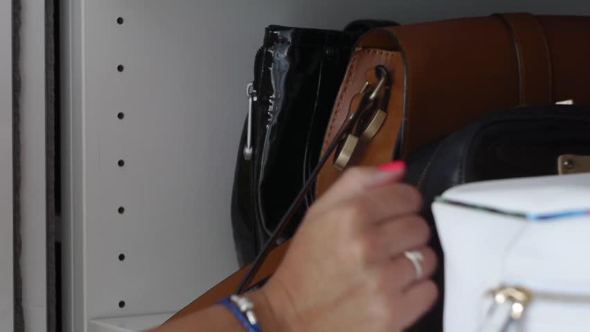 Woman Choosing Between Her Bags Rummage in Wardrobe | Shutterstock HD Video #1014726026