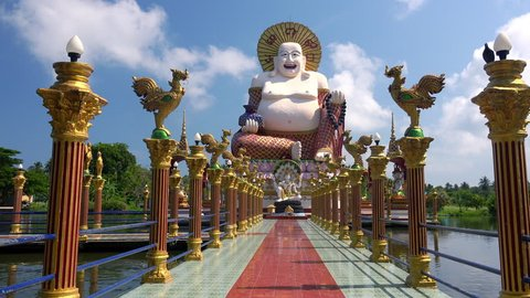 View of bridge decorated by golden statues of roosters and leading to large figure of happy Budai or Hotei. Giant sculpture of Buddhist deity at Wat Plai Laem temple complex, Koh Samui, Thailand.