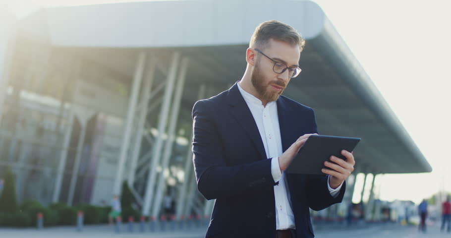 Portrait shot of the Caucasian young office worker in the glasses using his tablet computer - scrolling, taping and texting while standing near the big modern building, airport or train station.