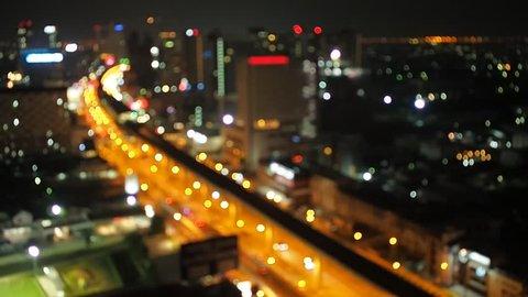 Defocused night city traffic road lights in Bangkok with transportation MRT Metro Rail Transit and car driving.