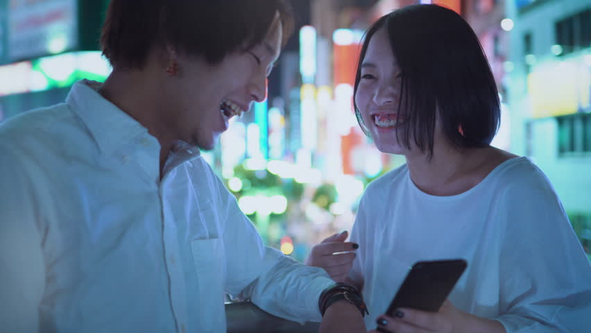 Young East Japanese Boy and Girl Couple Talking, Laughing, Using Mobile Phone and Sharing Screen. In the Background Blurred Advertising Billboards and City Lights at Night.
