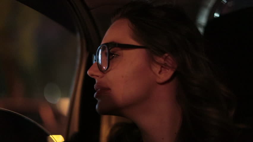 Woman looking out car window at night. Woman starring at city lights