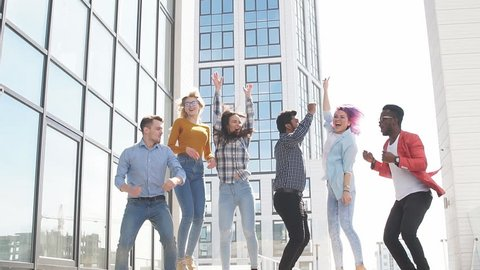 Group of multi ethnic young friends dressed in casual cloth having fun on lounge outdoor area on the roof of office glass building