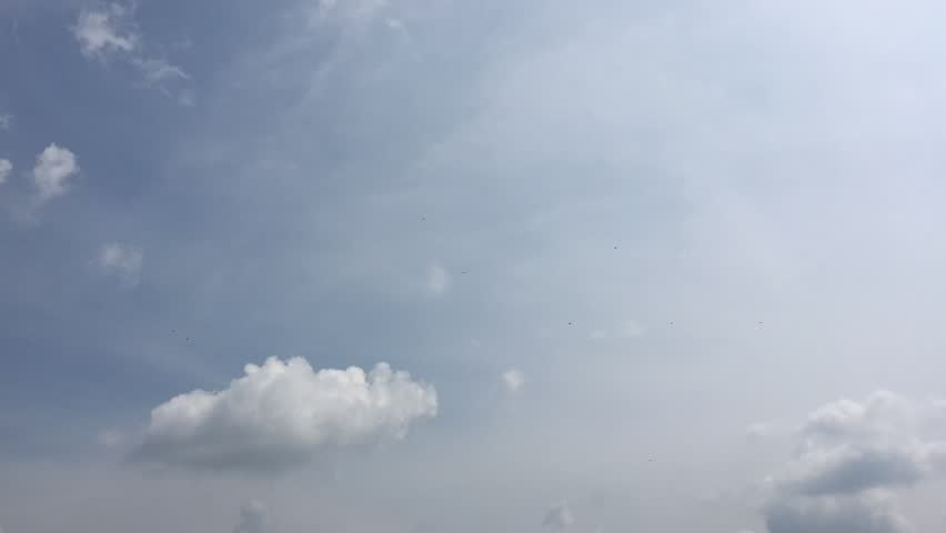 White clouds disappear in the hot sun on blue sky. Time-lapse motion cloud blue sky background. Blue sky with white clouds and sun.