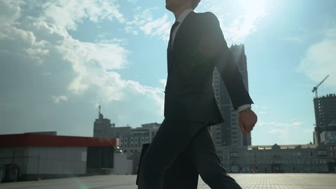 Handsome businessman walking around city, successful and self-confident man