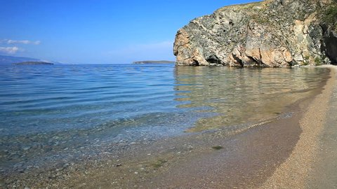 Lake Baikal. Olkhon Island on a summer sunny day. Transparent water of the shallow sandy bay near the rock with grottoes. Natural sounds of waves