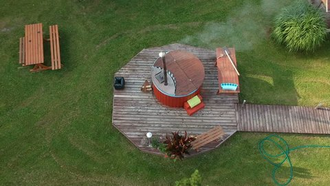 Outdoor bathhouse with hot water tub in yard, aerial view