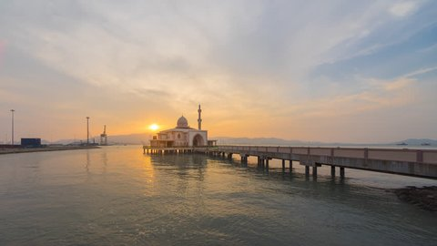 Beautiful sunrise time lapse of a floating mosque at the end of a jetty at a port in Malaysia at dawn from night to day. Prores Full HD 1080p.