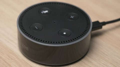 MONTREAL, CANADA - August 2018 : Closeup shot of a smart home voice activated assistant being used. Lighting up. Amazon Alexa Echo