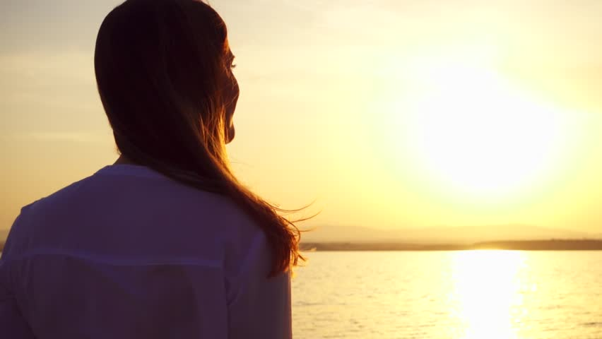 Dark silhouette of smiling young woman at sunset on lake enjoying quiet moment in nature. Close up of carefree female figure meditating at golden hour in slow motion #1014888496