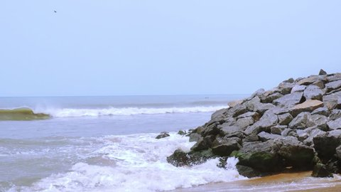 Waves dashing on a rocky outcrop of rock during day at Kovalam beach in chennai. Shot during the day it shows a rock sand beach on the outskirts of the indian city of chennai and a popular tourist