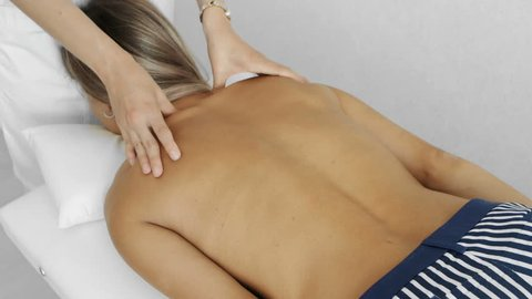 Neurologist examining female back and neck, moving her head, scoliosis treatment