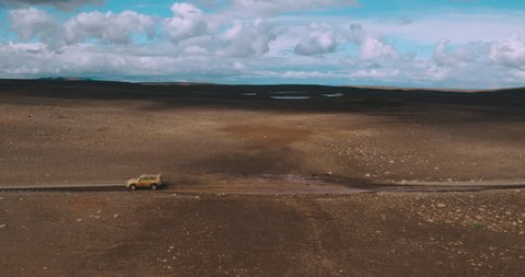 Aerial shot of 4x4 SUV car driving through puddle on isolated dirt road in desert landscape