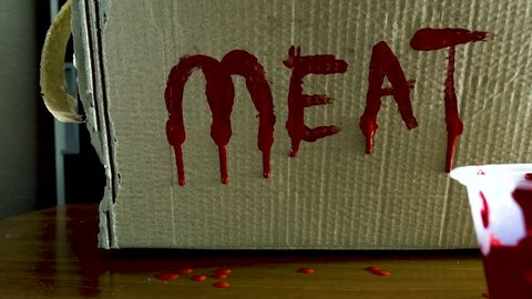 MEAT written in red paint dripping on cardboard