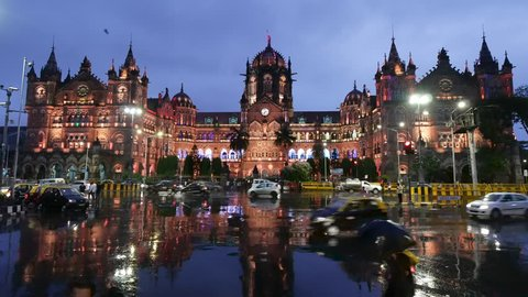 Mumbai, India: August 12, 2018: Chhatrapati Shivaji Terminus (CST) formerly Victoria Terminus is a UNESCO World Heritage Site and historic railway station in rain with reflection on wet road.