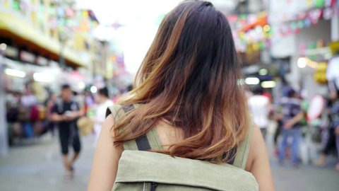 Traveler backpacker asian woman travel in Khao San road at Bangkok, Thailand. Happy young female spending holiday trip at amazing landmark and enjoy her journey in traditional city.