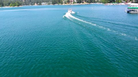 Fast Drone Shot Ascending Over and Overtaking a Pontoon Boat on Lake Arrowhead in Southern California