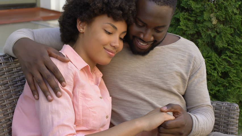 Happy african couple hugging on bench, outdoor date in city cafe, closeness #1014982126