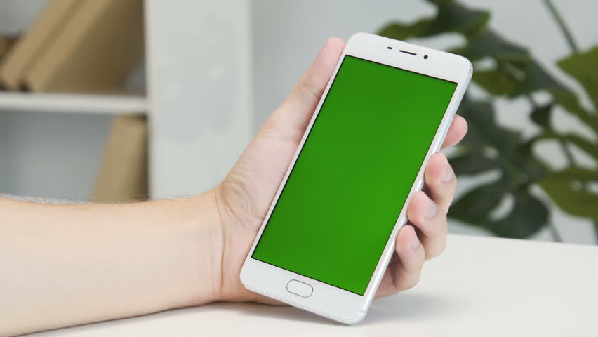 Hands using white modern smartphone with green screen at office with white walls and book shelf. Three swipes and touch. Close up. #1014992326