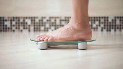 Male feet standing on electronic scales for weight control  on the bathroom.