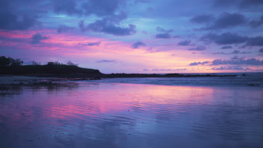 Beautiful out of focus background plate of purple and blue sunset on the beach in Costa Rica for compositing or keying. Blurred or defocused shot of ocean sun set for green screen composite. 4k