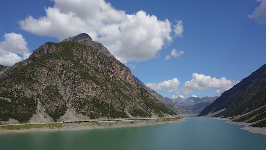 Drone aerial view of the Lake Livigno an alpine artificial lake and the road protected by avalanches. Italian Alps. Italy