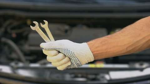 Closeup of hand holding spanners, repairing car in garage, upgrading vehicle
