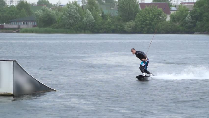 Handsome guy in a wetsuit is riding a wakeboard on the river   Shutterstock HD Video #1015067056