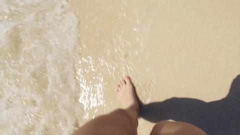 woman walk on sand beach, waves with algae gentle wash his feet. Summer. First person view
