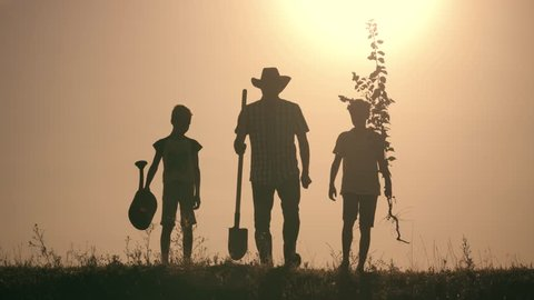 A happy family. Father and two sons plant and water the tree in the park at sunset. The concept of a happy family