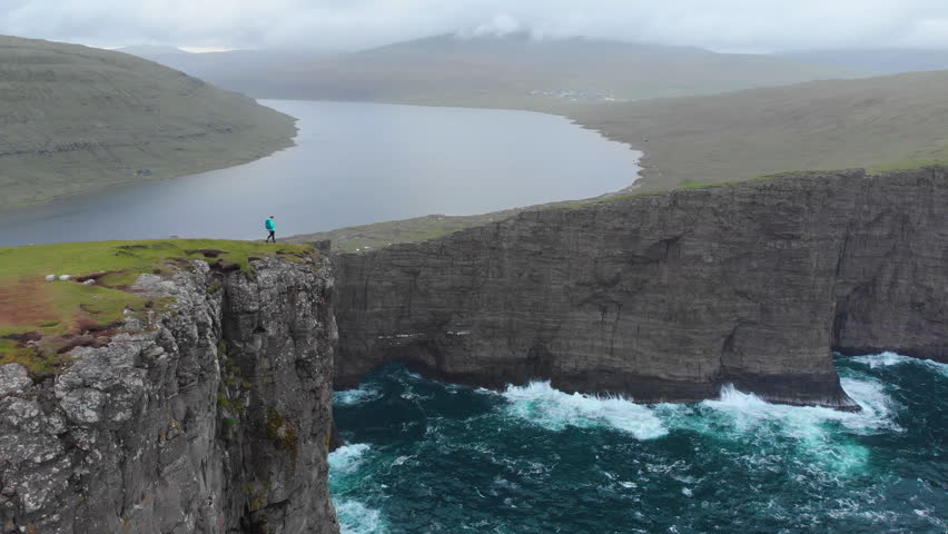 AERIAL COPY SPACE: Female hiker observing the towering cliffs and a still lake on a gray cloudy day in picturesque Faroe Islands. Spectacular view of young woman trekking in breathtaking rugged nature