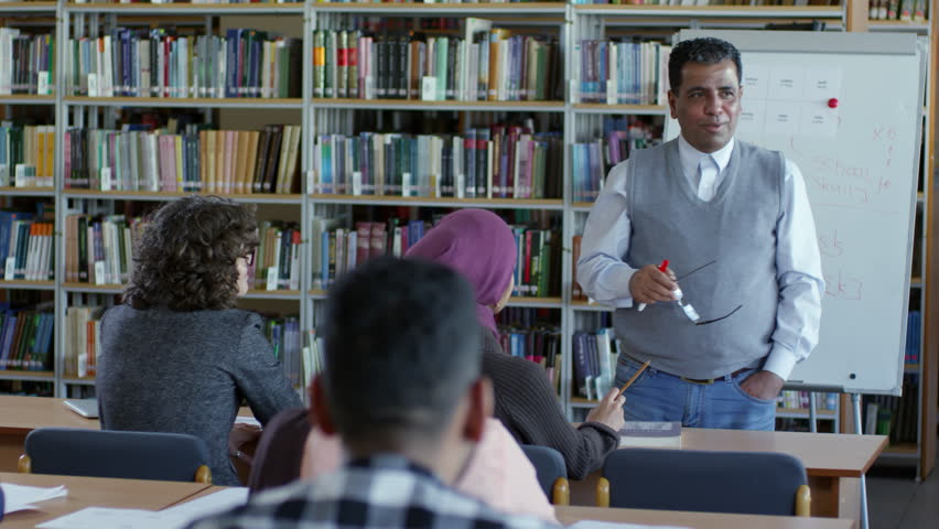 Tilt down of experienced middle eastern male teacher explaining lesson to migrant students in classroom with book racks and flipchart